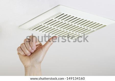Close up horizontal photo of female hand giving thumbs up after cleaning and installing bathroom fan vent cover from ceiling  - stock photo
