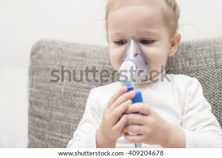 close up horizontal portrait of a little girl sitting on gray couch holding a nebuliser with her hands on her face on a white background