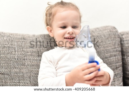 close up horizontal portrait of a little girl sitting on gray couch holding an asthma inhaler with her hands in front of her face and smiling and looking positive and healthy - stock photo