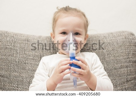 close up horizontal portrait of a little girl sitting on gray couch holding an asthma inhaler with her hands on her face and smiling and looking positive and healthy - stock photo