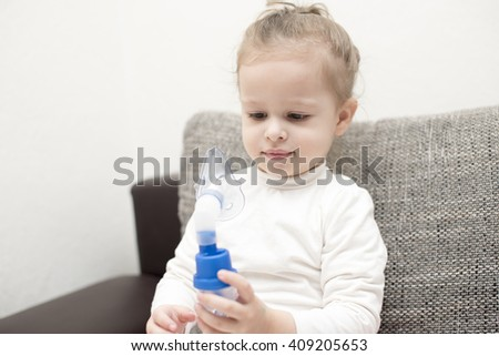 close up horizontal portrait of a little girl sitting on gray couch holding an asthma spray mask with her hands in front of her face and smiling and looking positive and healthy