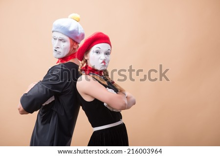 Close-up horizontal portrait of couple of two funny mimes looking irritating at the camera isolated on beige background with copy place - stock photo