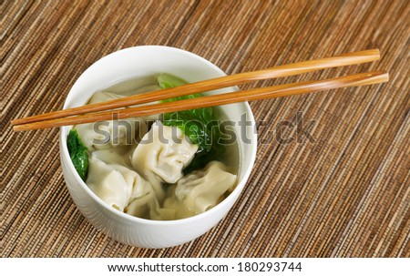 Close up horizontal top view photo of freshly made wonton with chopsticks on top of white bowl  - stock photo