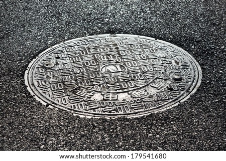 close-up horizontal view of new asphalt road and sewer manhole cover  - stock photo