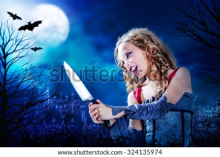 Close up horror portrait of Young female vampire holding big knife at dusk.Full moon and flaying bats over graveyard in Background.