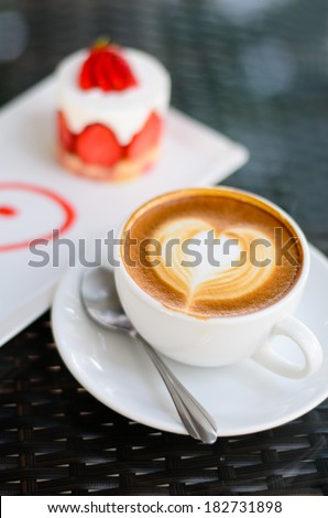 Close up hot coffee latte art and coffee foam with strawberry cake - stock photo