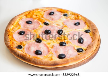 Close up Hot  meat pizza with ham  and olives on the wooden board isolated