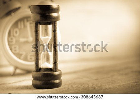 Close-up Hourglass on wood background , antique tone