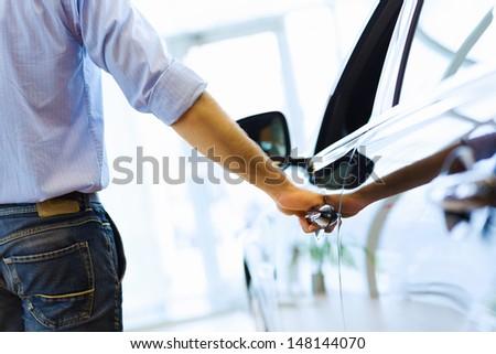 Close up human hand opening car door - stock photo