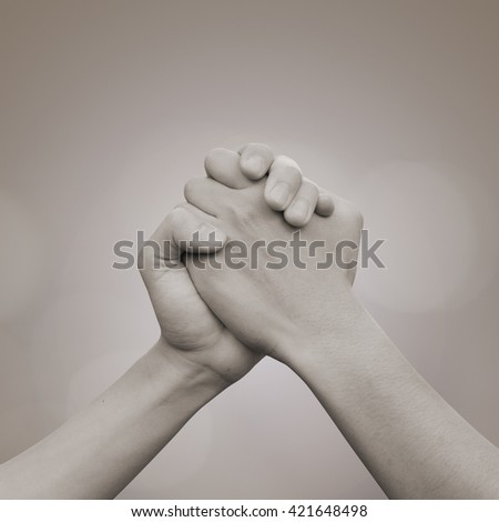 close up human handshake:man hands shake for confident,success,victory,assurance concept:trust and love of humanity conceptual idea.square frame picture:vintage tan tone color picture - stock photo
