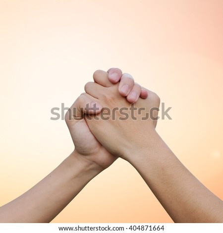 close up human handshake on gold orange colorful background with light:man hands shake for confident,success,victory,assurance concept:trust honesty of humanity conceptual idea.square frame picture - stock photo