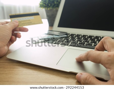 close-up human's hand using laptop computer for shopping online or online payment at home.