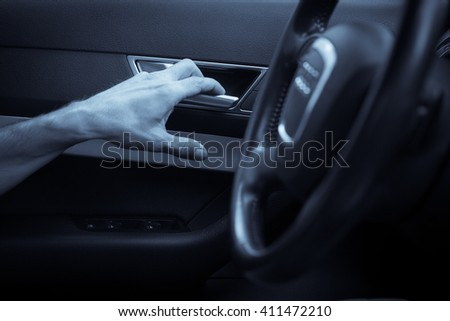 Close up image a hand opening a car door from inside.
