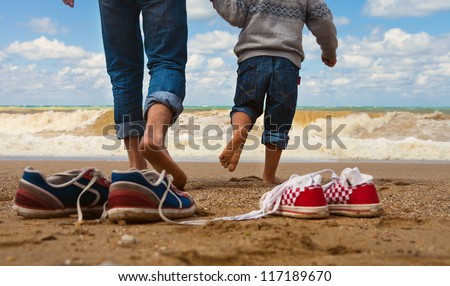 Close up image father and son legs walk at the seaside - stock photo