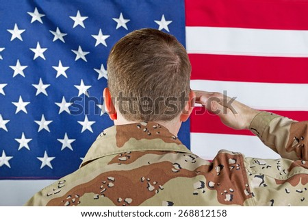 Close up image male soldier, back to camera, saluting United States of America flag while indoors not wearing hear gear.  - stock photo