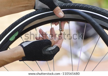 Close up image of a bicycle repair, with two hands in biker gloves, with valve, tube, alloys and a bike in the blurred background. - stock photo