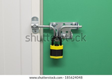 Close up image of a Black and Yellow on a self storage unit with a green door - stock photo