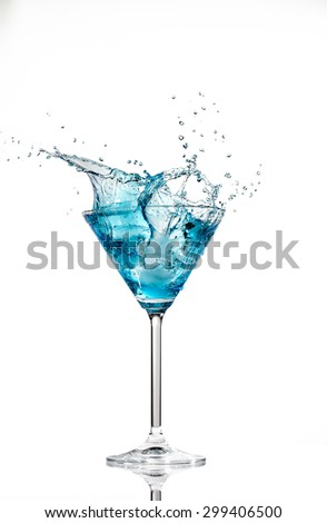 Close up image of a blue cocktail in a martini glass with an ice cube splashing into the liquid against a white background in studio