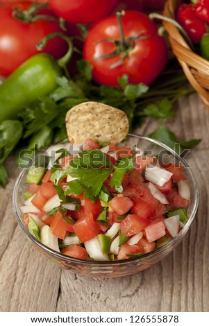 Close-up image of a bowl of Mexican salsa with chips and vegetables on the background - stock photo