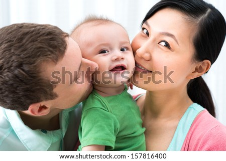 Close-up image of a cheerful family with a funny little boy on the foreground - stock photo