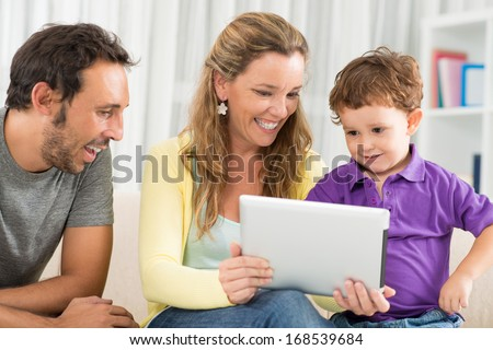 Close up image of a cheerful mother showing something funny on the tablet to her little son on the foreground  - stock photo