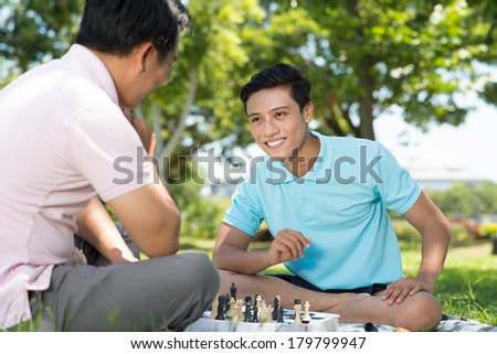 Close-up image of a cheerful teenage boy playing chess with his father on the foreground