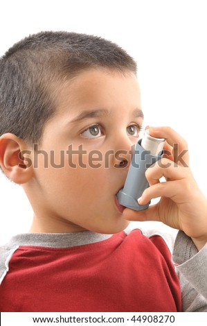 Close up image of a cute little boy using inhaler by himself for asthma. White background vertical studio picture. - stock photo