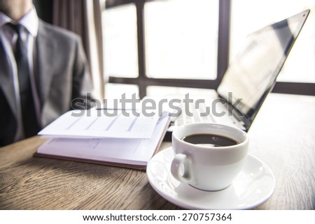 Close-up image of a desk at morning with a cup of coffee, laptop and notebook. - stock photo