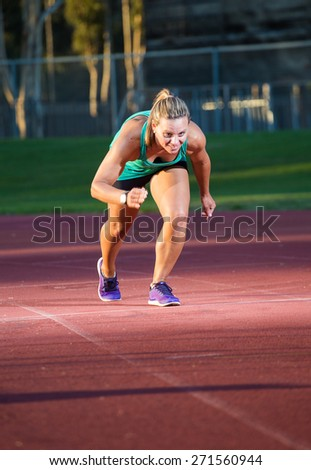 Close up image of a female sprinter / athlete on a tarmac athletics track. Photographed in moody light to give a dramatic effect with intentional motion blur. - stock photo