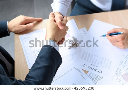Close-up image of a firm handshake between two colleagues after signing a contract - stock photo