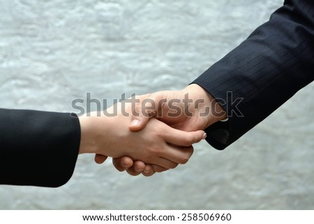 Close-up image of a firm handshake withe man and women