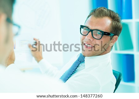 Close-up image of a handsome young businessman on the foreground - stock photo