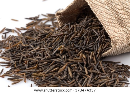 Close up image of a heap of wild rice on white background in a hessian sack
