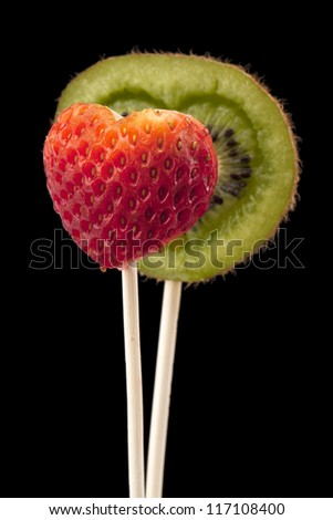 Close up image of a heart shaped kiwi and strawberry on dark background - stock photo