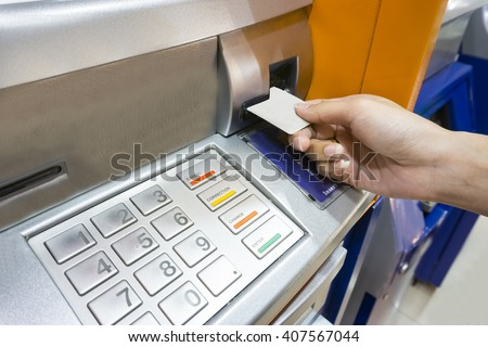 Close up image of a human hand inserting a credit card in the ATM - stock photo