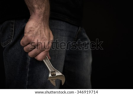 Close up image of a man in jeans and a t shirt holding a wrench at his side in front of a black background.