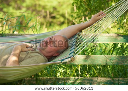 Close up image of a man relaxing in the shade in a hammock on a hot summer day. - stock photo