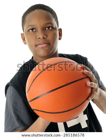 Close-up image of a preteen basketball player prepared to make a basket.  On a white background. - stock photo