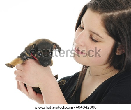 Close-up image of a pretty teen girl happily holding her tiny new puppy.  On a white background. - stock photo