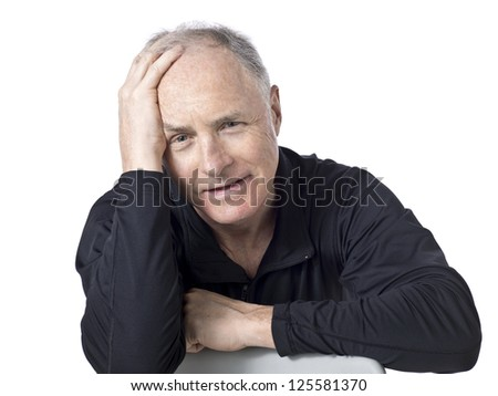 Close-up image of a problematic senior man sitting on the chair against the white surface - stock photo