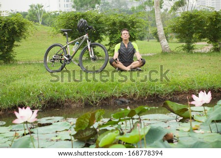 Close up image of a relaxed cyclist sitting in lotus posture near the bicycle on the foreground  - stock photo