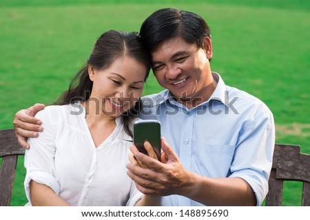 Close-up image of a senior man and a woman sitting together and making a self-portrait on a smartphone - stock photo