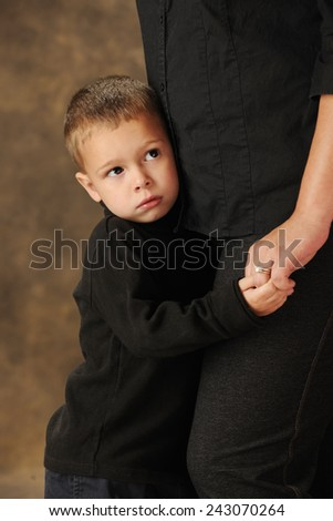Close-up image of a shy preschooler clinging closely to his mother.  Shallow DOF with focus on boy's face. - stock photo