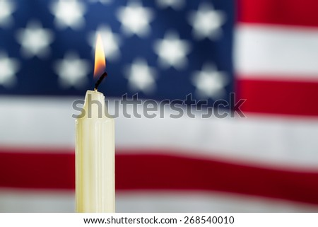 Close up image of a single white candle and glowing flame with United States of America flag in background. Fourth of July holiday concept.  - stock photo