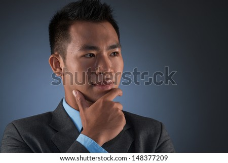 Close-up image of a thoughtful businessman with chin-on-hand against a grey background