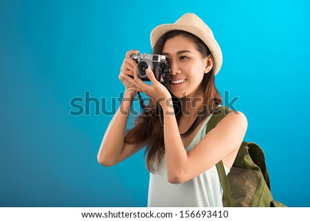 Close-up image of a traveler making a photo of something over a blue background - stock photo