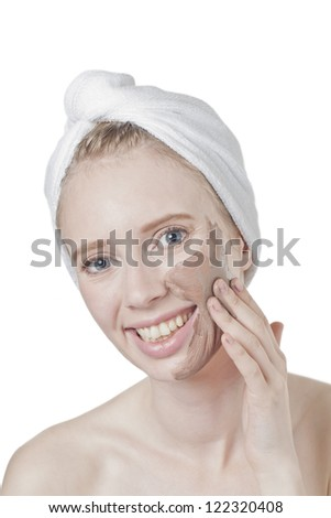 Close-up image of a woman's face with spa clay mask and smiling on a white background