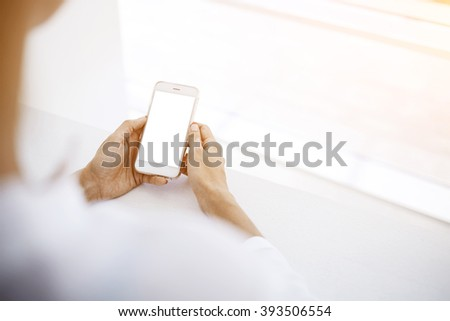 Close up image of a woman`s hands is holding cell telephone with mock up copy space screen for your advertising text message. Female reading information on web page via mobile phone during work break - stock photo