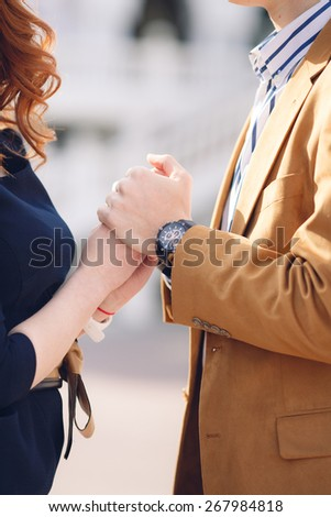Close-up image of a young couple holding hands. Conceptual image of female and male hands together - stock photo