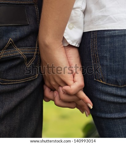 Close-up image of a young couple holding hands outdoor - stock photo